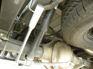 Use open end wrench on bolt head, socket and breaker bar on nut end. Wrench sizes used are different on each shock end.
